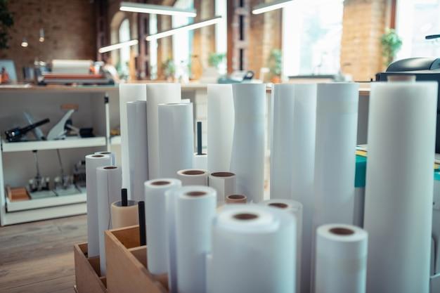 紙のロール。明るく広々としたオフィスに立っている本を印刷するための紙のロール