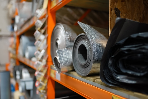 Рулоны теплоизоляции в хозяйственном магазине крупным планом. материалы для строительства и ремонта на полке своими руками