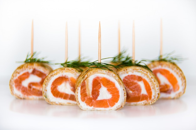 Rolls of pancakes filled with smoked salmon and cream cheese