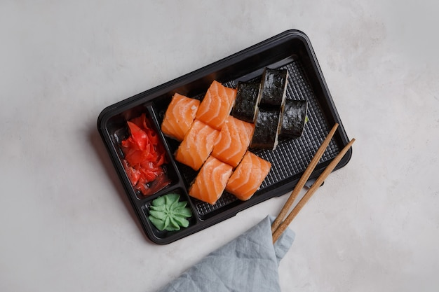 Rolls in a plastic container, pink ginger, wasabi, sushi delivery concept. ordering japanese food