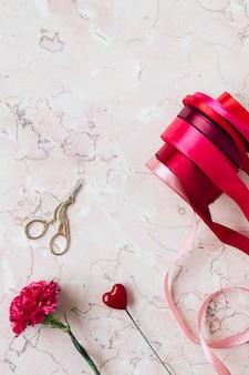 粉红色大理石背景上的红丝带卷