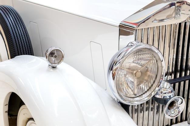 Передние фары и радиатор на старом эксклюзивном rolls-royce винтажном автомобиле крупным планом.