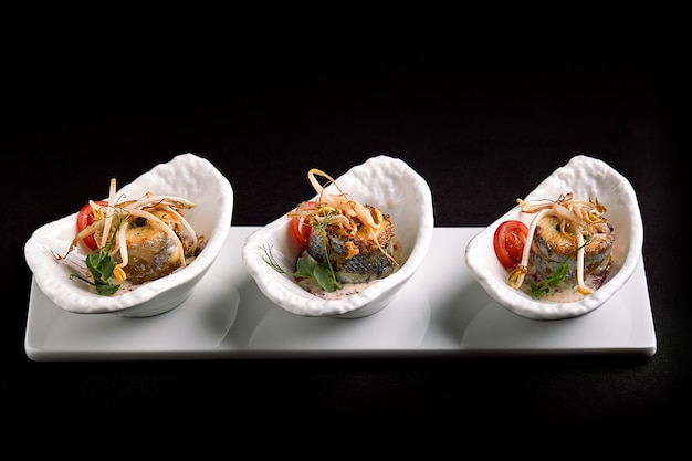 Rolls of sea bass baked stuffed with vegetables and mushroom sauce