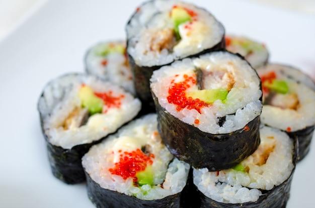 白いプレートと明るい表面にロールパン、寿司、生姜。