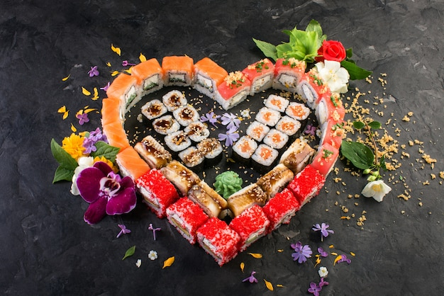 Rolls and sushi on a black slate background, japanese cuisine