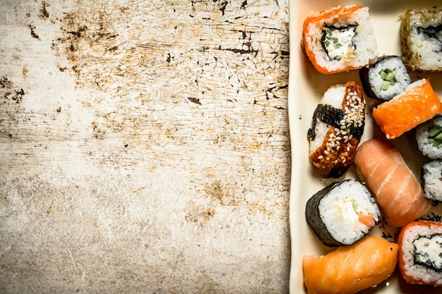The rolls and sushi, seafood on the plate. on rustic background.