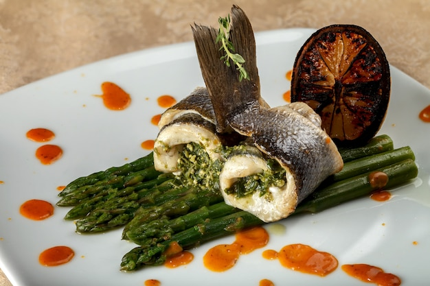 Rolls of white baked fish with asparagus sauce