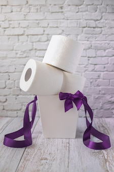 Rolls of white toilet paper lie in white gift box with purple ribbons and bow, vertical orientation
