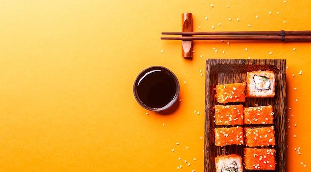 Роллы с палочками на изолированном оранжевом фоне