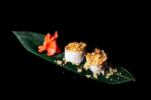 Rolls with crackers in the top on a green leaf with ginger in dark space.