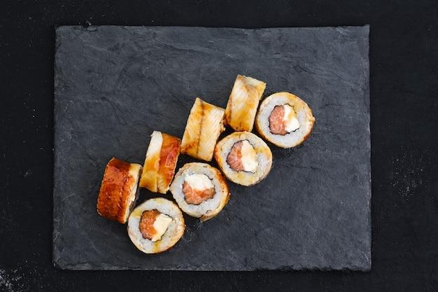 Роллы с угрем и сливочным сыром на грифельной тарелке