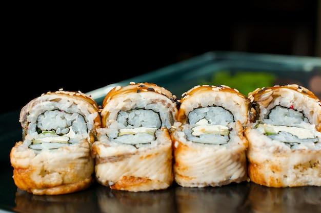 장어, 아보카도, 오이, 크림 치즈, 노리, 흰색과 검은색 참깨가 클로즈업된 롤. 일본 전통 요리.