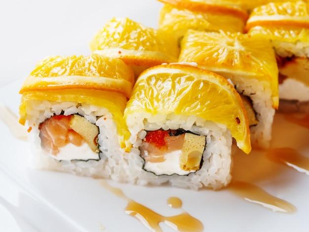 Rolls with rice, seaweed nori, salmon, cream cheese, chicken egg, caviar masago, orange.