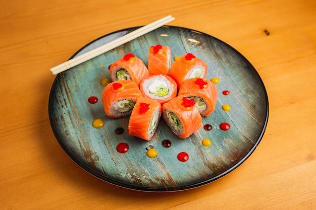 Роллы с лососем, украшенные икрой летучей рыбы на синей тарелке