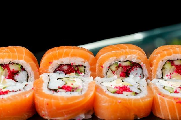연어, 토비코 캐비어, 아보카도, 오이, 노리 클로즈업이 있는 롤. 일본 전통 요리.