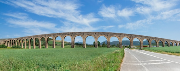 Roman aqueduct and road on grass and sky background spain