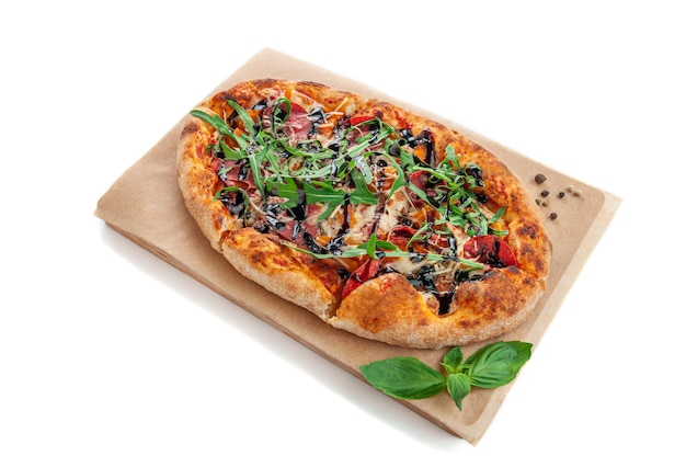 Roman pizza with roasted vegetables arugula and balsamic sauce on a wooden tray. decorated with basil and spices. white background. isolated.