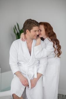 ロマンス。抱き合って恋をしている白いバスローブを着たカップル