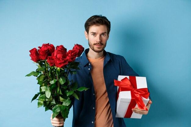 Романтика и день святого валентина. мужчина преподносит любовнику букет красных роз. парень приносит цветы и подарок на романтическое свидание, стоя на синем фоне.