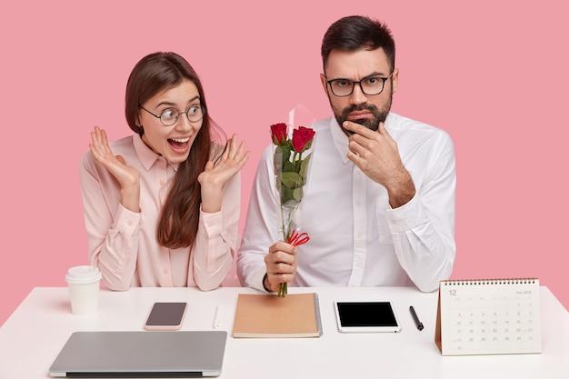 작업 개념에서 로맨스. 상사로부터 꽃다발을 받고 연인이 된 즐거운 여성 비서가 현대 전자 기기로 데스크탑에 앉아