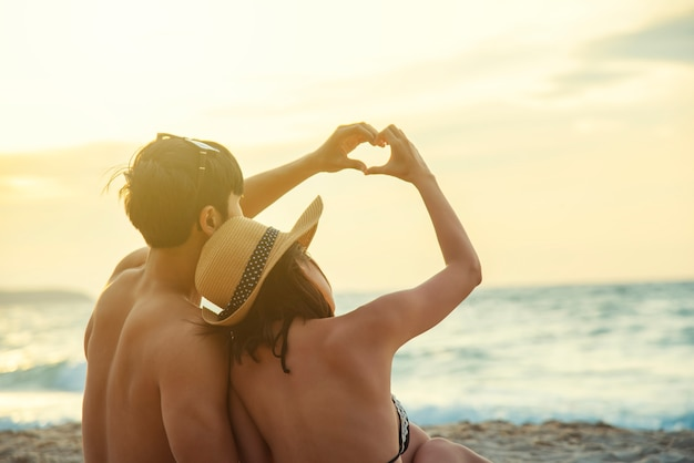 Romance couple made a heart shape together by hands on the beach at sunset.