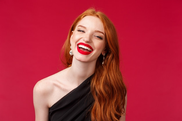 Romance, elegance, beauty and women concept. close-up portrait of happy, cheerful redhead woman in luxurious black dress, red lipstick, enjoying party or date, laughing beaming smile