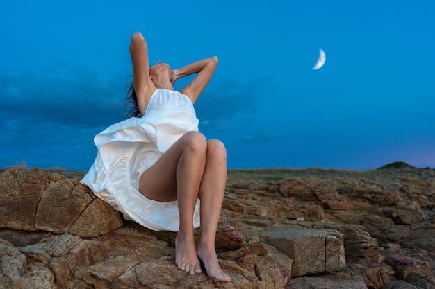 Романтическая фантастическая сцена с красивой молодой женщиной, держащей волосы, глядя вверх на ветру, поднимает свое длинное белое платье, показывая ее ноги