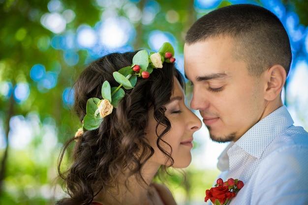 緑豊かな公園で若い愛情のある美しいカップルのロマンス。