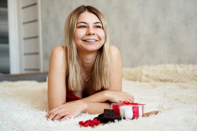 Романтика, концепция подарков на день святого валентина. красивая блондинка женщина на диване с подарками