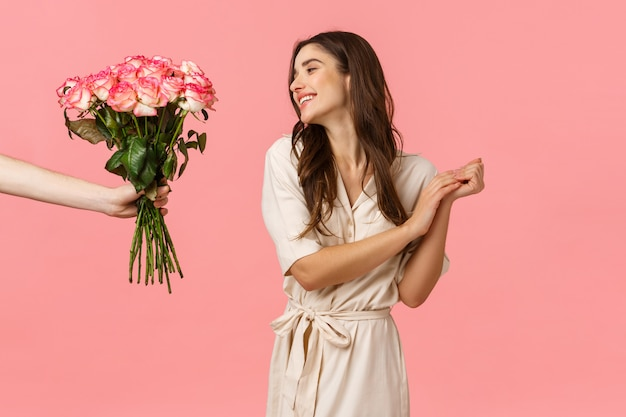 Romance, valentines day, love concept. charming feminine young woman sighing romantic and delighted, looking at hand giving her flowers, beautiful bouquet roses, feeling cherished, pink wall