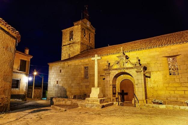 밤에 종탑과 돌 십자가가 있는 로마네스크 양식의 교회.