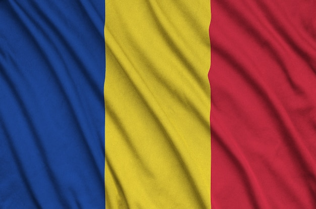 Romania flag  is depicted on a sports cloth fabric with many folds. sport team