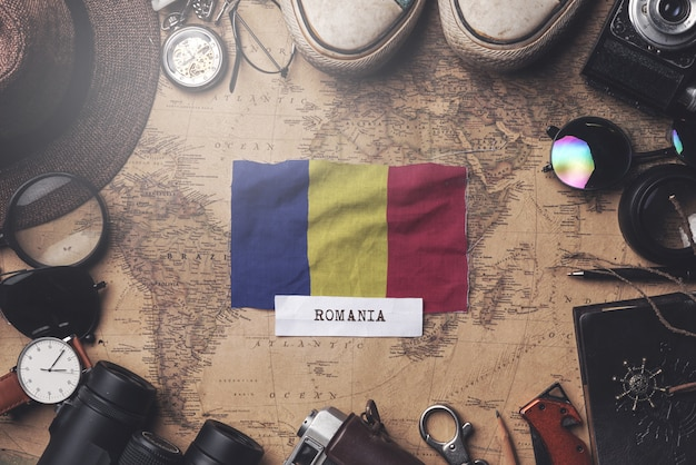 Romania flag between traveler's accessories on old vintage map. overhead shot