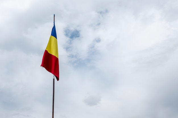 Romanian flag on flagpole blowing in wind isolated on blue sky