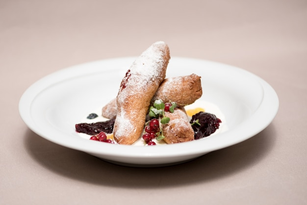 Romanian traditional sweets - cheese pancakes with sour cream, jam and decorated with forest fruits