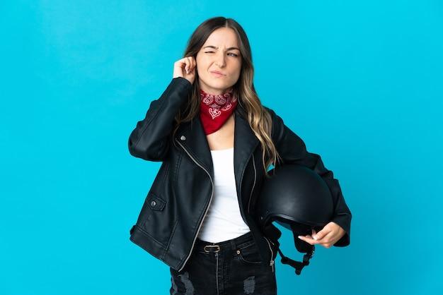 Румынская женщина, держащая мотоциклетный шлем, изолирована на синем, разочарована и закрывает уши