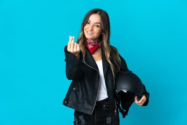 お金のジェスチャーを稼ぐ青いスペースに分離されたオートバイのヘルメットを保持しているルーマニアの女性