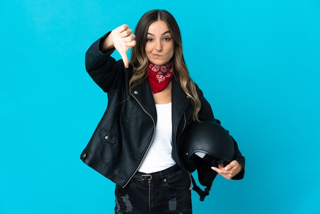 Romanian woman holding a motorcycle helmet isolated on blue background showing thumb down with negative expression