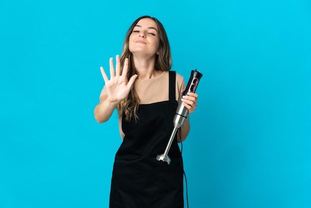 指で5を数える青い壁に分離されたハンドブレンダーを使用してルーマニアの女性