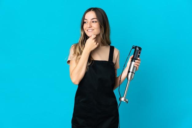 Румынская женщина, использующая ручной блендер, изолирована на синей стене, глядя в сторону и улыбается