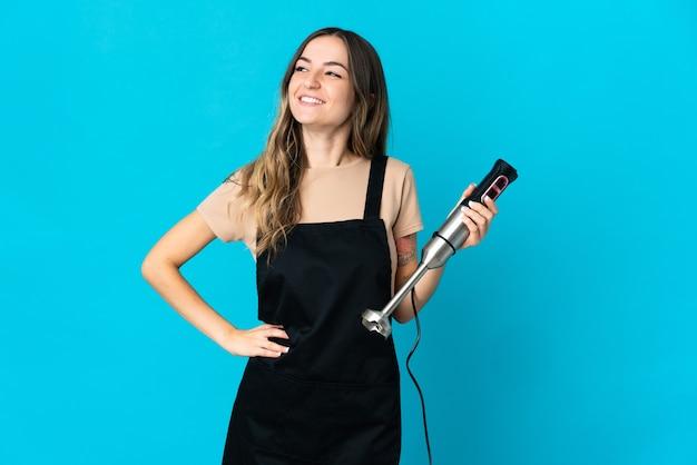 Румынская женщина использует ручной блендер, изолированную на синей стене, позирует с руками на бедрах и улыбается