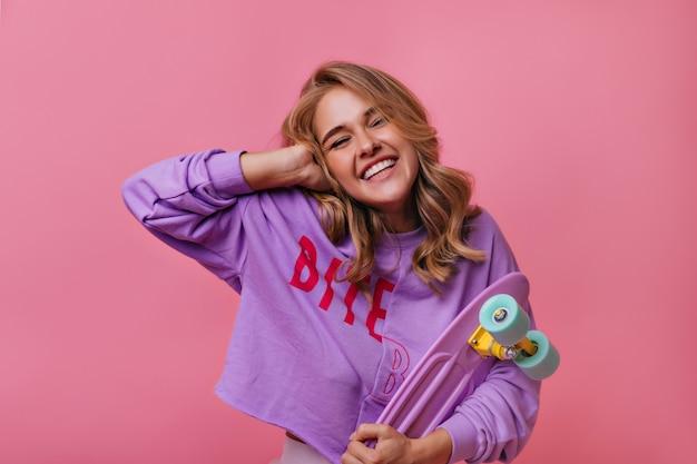Романтичная активная девушка позирует с longboard. крытый портрет великолепной блондинки, держащей скейтборд на розовом.