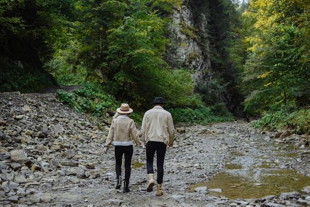 若い観光客のカップルのロマンチックな冒険、山のハイキングコースに向かって手をつないで上り坂に行く男女の低角度