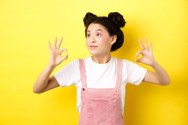 左のロゴを見て、承認の大丈夫な兆候を示し、黄色の上に立っているロマンチックで美しいアジアの女の子。