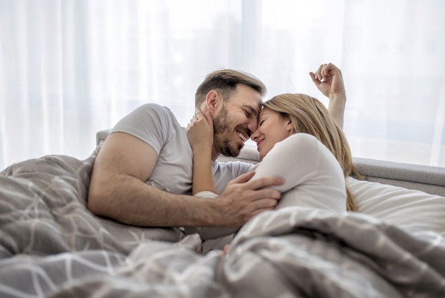 Романтическая и милая пара, лежа в постели и обнимая друг друга