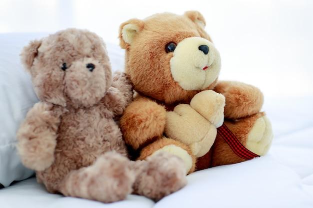 두 개의 갈색 사랑스러운 푹신한 테디 베어 장난감의 개념이 있는 침실의 낭만적이고 즐거운 분위기는 달콤한 친구가 재미있는 놀이를 하는 것처럼 근처에 창의적으로 배치됩니다.