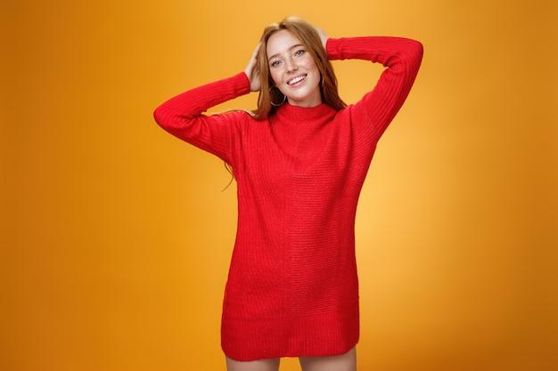 우아하고 따뜻한 붉은 겨울 드레스를 입은 로맨틱하고 관능적인 귀여운 생강 여자친구는 머리 뒤에 손을 잡고 편안하고 근심 없는 미소를 지으며 여가와 휴가를 즐기며 기뻐하며 고개를 기울이고 있습니다.