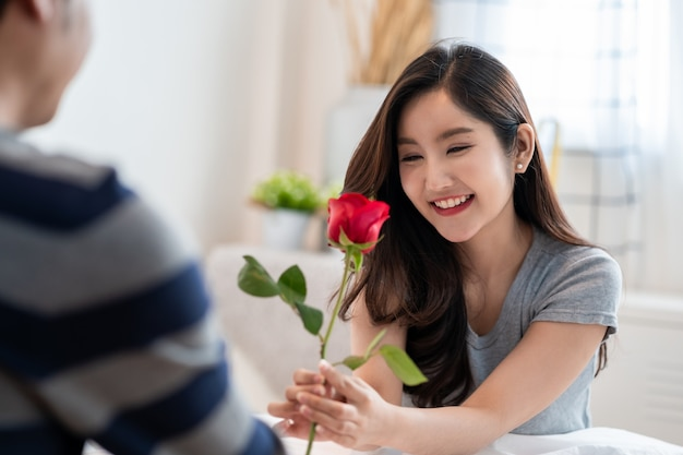 침실에 있는 로맨틱한 아시아 커플, 아름다운 여성에게 장미를 주고 사랑과 행복으로 아름다운 장미에 키스하는 남자, 아름다운 우아한 아시아 커플이 침실에서 포옹하고 웃고 있습니다