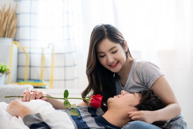寝室でロマンチックなアジアのカップルはきれいな女性に赤いバラを与える若い男