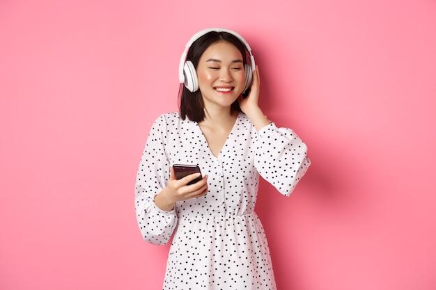Romantica ragazza asiatica che ascolta musica in cuffia, sorride con gli occhi chiusi, tiene in mano il cellulare, in piedi su sfondo rosa